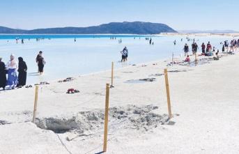 """Tatilciler, """"çamuru cilde iyi geliyor"""" diyerek Salda Gölü sahilinde birden fazla çukur açtı"""